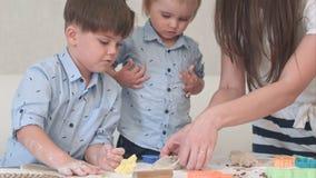 Niños pequeños lindos que ruedan la pasta para las galletas así como mamá Foto de archivo libre de regalías