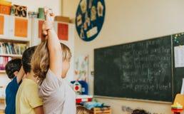 Niños pequeños lindos que trabajan en sala de clase Foto de archivo