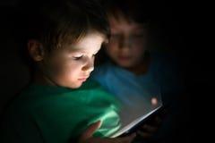 Niños pequeños que juegan en la tableta en la noche Fotos de archivo