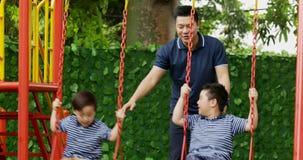 Niños pequeños y padre que juegan en el oscilación almacen de video