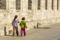Niños pobres que caminan a lo largo de la pared Fotos de archivo libres de regalías