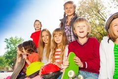 Niños positivos con los monopatines y los cascos Imagen de archivo libre de regalías