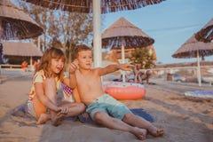 Niños positivos felices que hablan y que juegan en la playa imagen de archivo