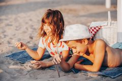 Niños positivos felices que juegan con la arena y hablar imágenes de archivo libres de regalías
