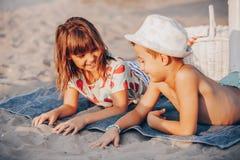 Niños positivos felices que juegan en la playa fotos de archivo