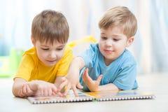 Niños preciosos que leen un libro, en el piso en Fotos de archivo libres de regalías