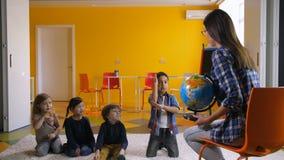 Niños preescolares que estudian el globo así como profesor almacen de metraje de vídeo