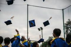 Niños preescolares que llevan el casquillo y al diplomático que lanzan graduados del vestido en cielo en día graduado de la celeb imagen de archivo