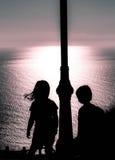 Niños puesta del sol y horizonte retroiluminados Foto de archivo