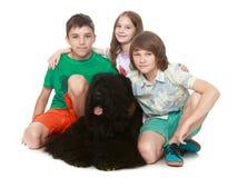 Niños que abrazan el perro grande Foto de archivo