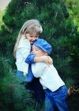 Niños que abrazan en árboles de pino Fotos de archivo
