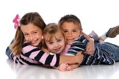 Niños que abrazan la colocación en el suelo Imagenes de archivo