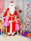 Niños que abrazan la helada de abuelo de los árboles de navidad Imagen de archivo