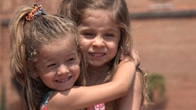 Niños que abrazan muchachas o a hermanas almacen de metraje de vídeo