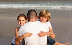 Niños que abrazan a su padre Fotos de archivo libres de regalías