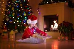 Niños que abren regalos de Navidad en la chimenea Fotografía de archivo