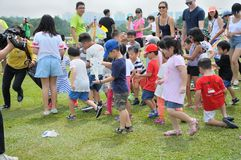 Niños que acometen para coger los mini-paracaídas fotografía de archivo libre de regalías