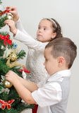 Niños que adornan el árbol de navidad Imagenes de archivo