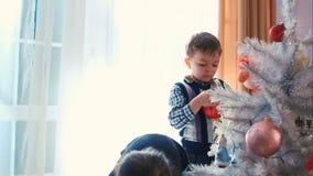 Niños que adornan el árbol de navidad almacen de metraje de vídeo