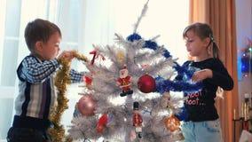 Niños que adornan el árbol de navidad con malla almacen de video