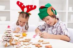 Niños que adornan las galletas del pan de jengibre Imágenes de archivo libres de regalías