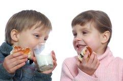 Niños que almuerzan con leche Imagenes de archivo