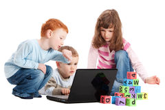 Niños que aprenden con las cartas y el ordenador de los cabritos Foto de archivo libre de regalías