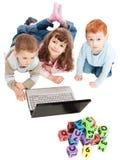 Niños que aprenden con los bloques y el ordenador de los cabritos Imagenes de archivo