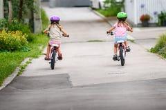 Niños que aprenden conducir una bicicleta en una calzada afuera imagen de archivo libre de regalías