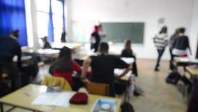 Niños que aprenden en escuela primaria Alumnos que ejercitan, escribiendo y discutiendo en una sala de clase Niños que estudian e metrajes