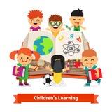 Niños que aprenden junto del libro grande de la enciclopedia Imagen de archivo libre de regalías