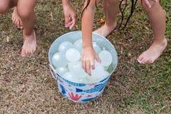 Niños que asen los globos de agua del cubo del metal fotografía de archivo