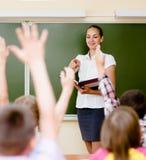 Niños que aumentan las manos que conocen la respuesta a la pregunta Fotos de archivo