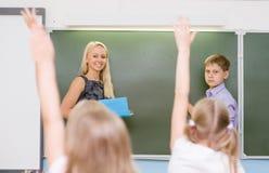 Niños que aumentan las manos que conocen la respuesta a la pregunta Foto de archivo libre de regalías