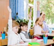 Niños que aumentan las manos que conocen la respuesta a la pregunta Imágenes de archivo libres de regalías
