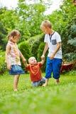 Niños que ayudan al bebé que aprende caminar Imagenes de archivo