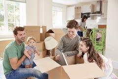 Niños que ayudan a padres a desempaquetar en la mudanza en día fotos de archivo