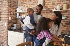 Niños que ayudan a padres a preparar la comida en cocina imagen de archivo