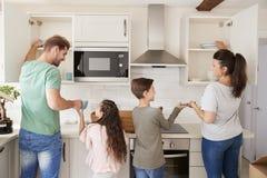 Niños que ayudan a poner la loza ausente en armarios de la cocina imagenes de archivo
