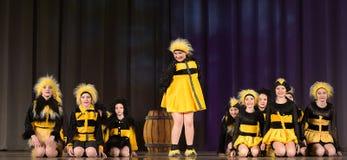 Niños que bailan en trajes de la abeja Fotos de archivo