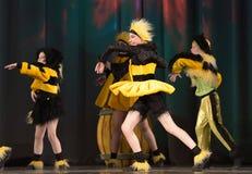 Niños que bailan en trajes de la abeja Imagenes de archivo