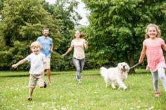 Niños que caminan el perro Imagenes de archivo