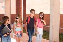 Niños que caminan en el campus de la escuela imagenes de archivo
