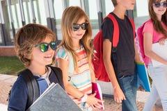 Niños que caminan en el campus de la escuela imágenes de archivo libres de regalías