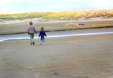 Niños que caminan en la playa Imagenes de archivo
