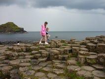 Niños que caminan en las columnas del basalto del terraplén del gigante Imagen de archivo