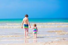 Niños que caminan en una playa Fotos de archivo