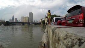 Niños que caminan a lo largo de jugar concreto de la orilla del río metrajes