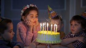 Niños que celebran la fiesta de cumpleaños y que soplan velas en la torta almacen de video