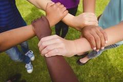 Niños que celebran las manos juntas en el parque Fotografía de archivo libre de regalías